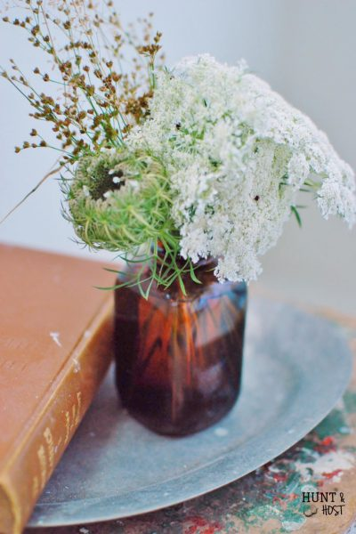 Wild flowers arranged in tobacco jars. www.huntandhost.net