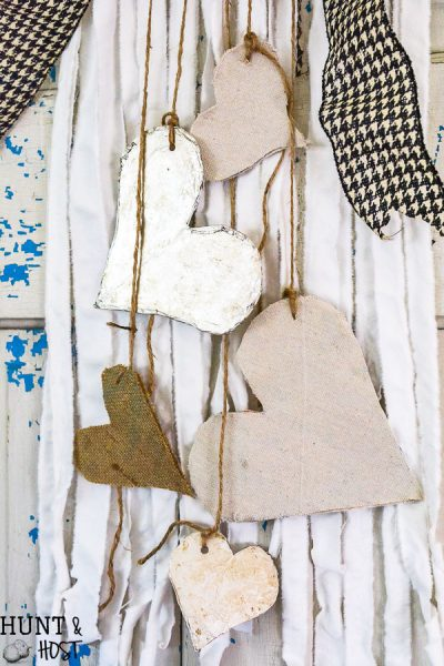 Create boho chic wall hanging decor from your old linens. Purging the linen closet will provide tons of great crafting material. This DIY wall hanging is dressed up for Valentine's Day, but would be great for a farmhouse feel any time of year. WIth great texture from burlap, drop cloth and tin foil this tone on tone neutral decor is a versatile addition to any style, Simple natural touches round out this Valentine home tour.