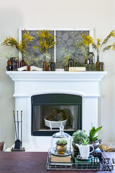Decorating the mantel for fall with amber glass jars and roadside dreid flowers.