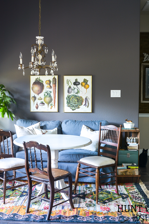 This moody boho vintage breakfast room takes advantage of the vibrant color palette popular in 2019 with a vintage chandelier, dark IKEAS sofa, vintage farmhouse prints and tons of texture you are sure to see some boho decorating ideas you can steal. #bohodecor #vintagestyle #breakfastroomdecor #moodycolors #coloroftheyear #painttrends2019 #vintagechandelier