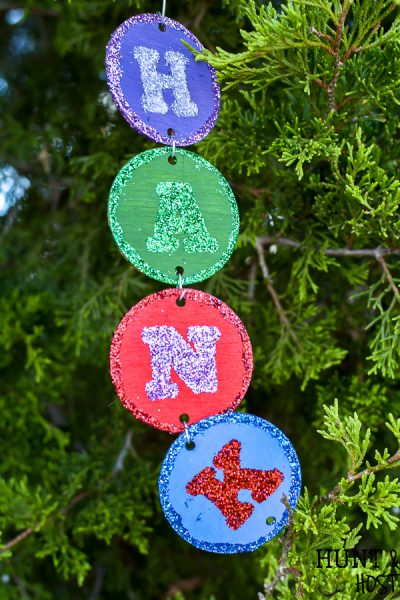 Make your own personalized Christmas ornament with your name, your kid's name or just fun Christmas sayings and words. This easy DIY takes no special tools or machines. You can make custom christmas ornaments to fit your color scheme and any name, even a christmas ornament for unusual names! Everyone loves to see their name in glitter and on the Christmas tree so make these special ornaments for the whole family. #handmadechristmas #christmastreeornaments #decoratethetree #nameinlights #DIYChristmasornament #glitter #easy #simpleChristmas