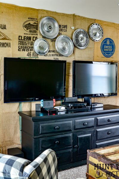 What a great game room idea! This rustic cabin lodge game room has great decorating ideas. a tutorial on how to hang a wall mounted TV (or two for a Fortnight lover's paradise!) plus an inexpensive DIY burlap wall covered in coffee bean sacks. All the elements for the perfect family game room with a cozy cabin style! #SANUS #SANUSspaces @SANUS @SANUSsystems #gameroomideas #burlapwalls #DIYwallpaper #mediaroom #TVmount #rusticroom #familyroomideas #rusticdecorideas