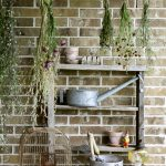 The perfect plant drying rack for your patio. If you want a French country feel on your porch then a vintage baby mattress spring is the best idea! Maybe you can even use it for a herb drying rack if you are a foodie! #herbdryingrack #diydryingrack #babybedidea#wildflowers #herbdrying #cozyporch #porchquilt
