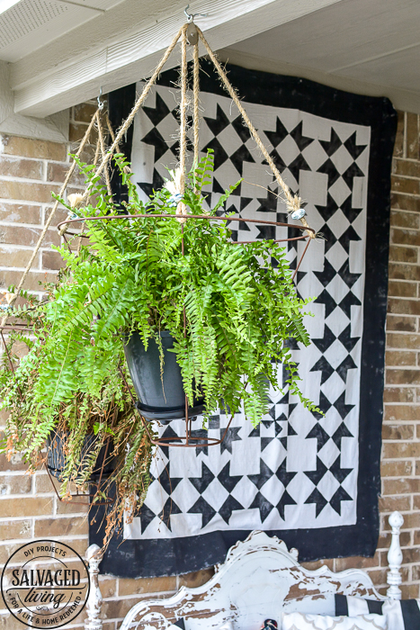Looking for an unusual outdoor hanging basket for your favorite patio plants? This vintage lampshade makes the perfect hanging basket and is a simple upcycle for your porch. #outdoorhangingbasket #industrialvintageporch #lampshadeideas #DIYplanthanger #diyhangingbasket #outdoorpatiodecor #fern #vintageporch