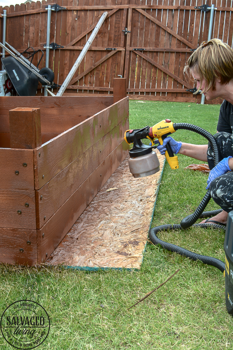Learn how to spray stain on wood along with tips on how to clean your sprayer when you spray an oil based stain. HINT: it is so much easier than you think! This DIY raised garden bed got a spray stain that will help the wood look good and last longer and it only took minutes to do,. #wagnerspraytech #spraystain #oilbasedstain #paintcleanup #sprayertips #stainedwood #flowergarden #vegetablegarden #raisedbed #landscapedecor #fencestain #diyfencestain