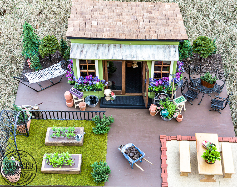 Tour a miniature vintage garden shop dollhouse for great ideas for your own dollhouse decor. See how to make a cozy home, lush garden and outdoor miniature yard! COmplete with garden gnomes, miniature potted plants and sitting areas. #dollhouse #miniatures #DIYdollhouse #vintagegarden #tinydecor