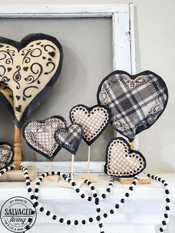 Learn how to make gorgeous giant paper hearts for Valentine's Day decorating on repurposed spindle stands. This dollar store craft is perfect for a farmhouse Valentine theme. #vintageValentine #upcycledprojectidea #spindle #papercraft #stencilart #valentinesdaymantel