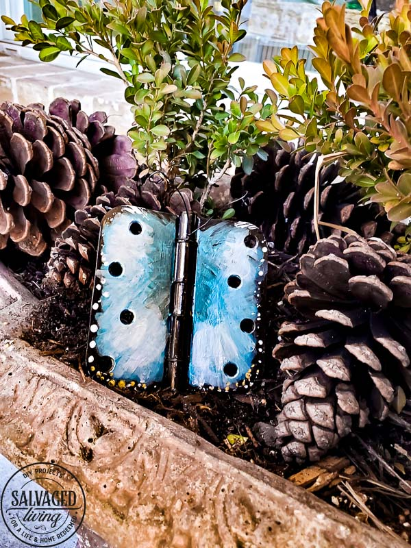 Wonder what to do with old door hinges? Try this upcycled door hinge butterfly project for a fun and beautiful addition to your spring decor ideas. These painted butterflies are perfect for your patio and potted plants. Truly adorable yard art you can DIY with thrifted or left over materials! #butterflyart #doorhinge #upcycledcraft #springdecor #springcraft