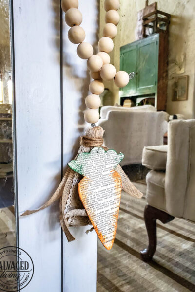 Dollar store wood cutouts for easter decor, this cute dollar Tree carrot craft is a beautiful way to add a wood bead tassel to your spring decor. #dollarstorecraft #dollartreedecor #woodcutout #beadgarlandDIY #DIYtassel