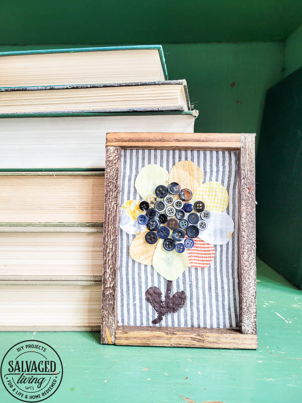 finished sunflower art in frame on table with books