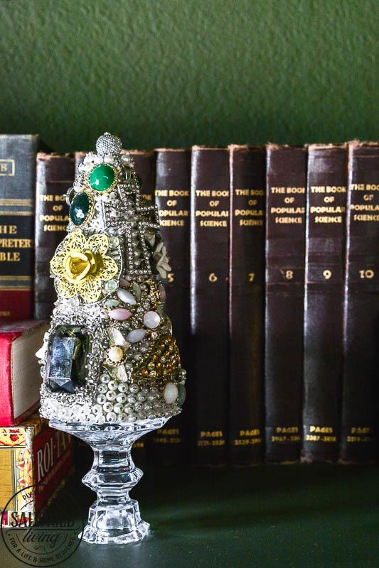 vintage jewelry tree next to books